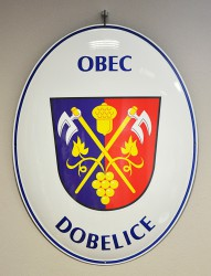 Oval welcome sign with a coat of arms and the name of a village/town/township